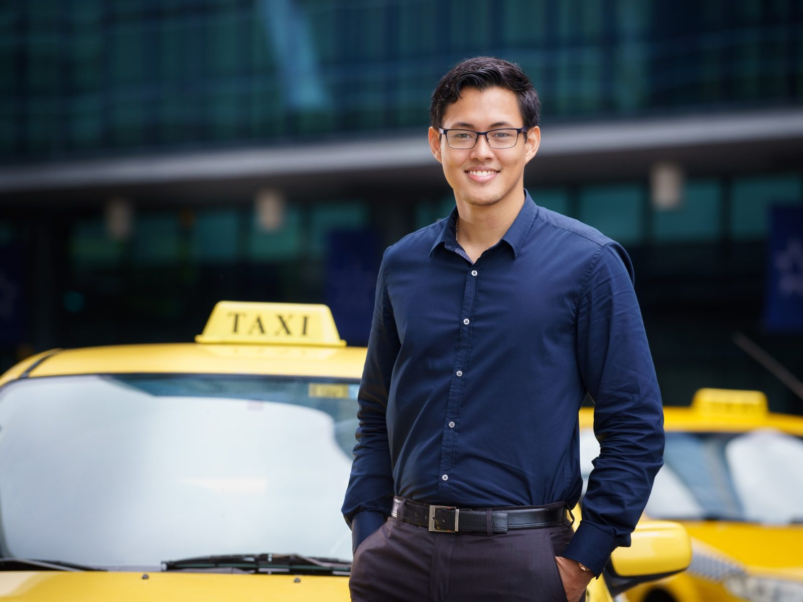 Portrait of happy chinese taxi driver leaning on yellow car with arms crossed, smiling and looking at camera by diego_cervo