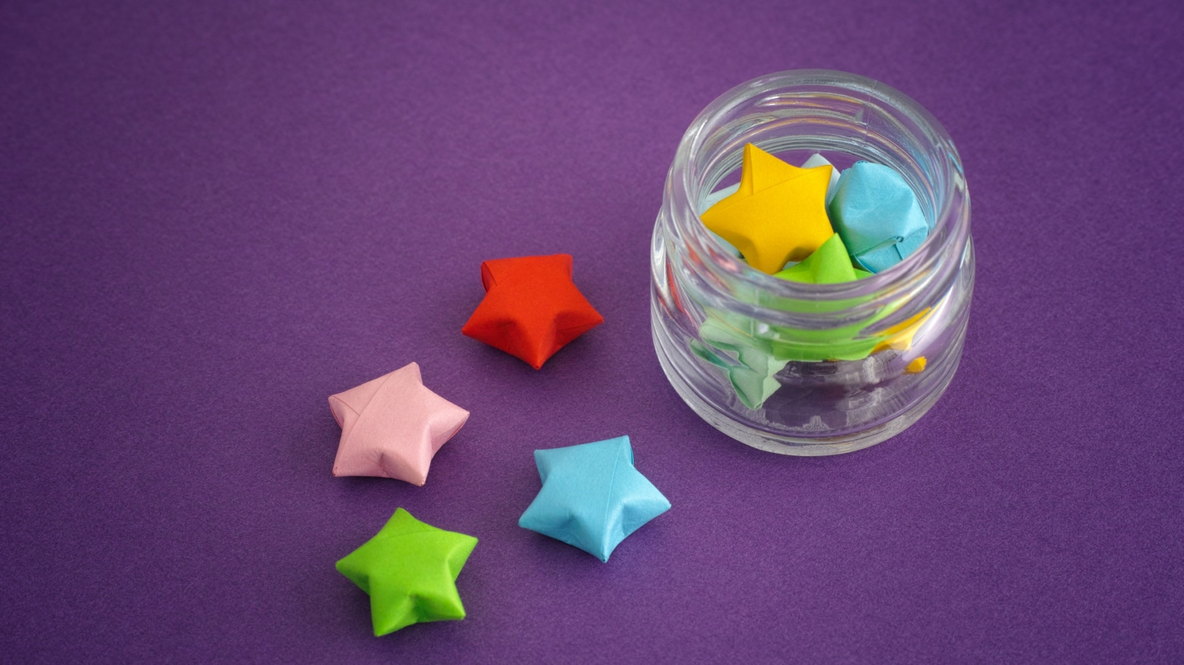 Colorful origami lucky stars spilling out of a jar by StepanPopov