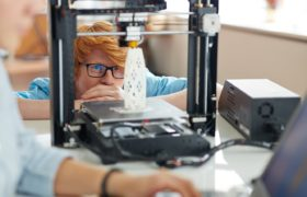 Engineer looking at architectural model in 3d printer in working environment by Pressmaster