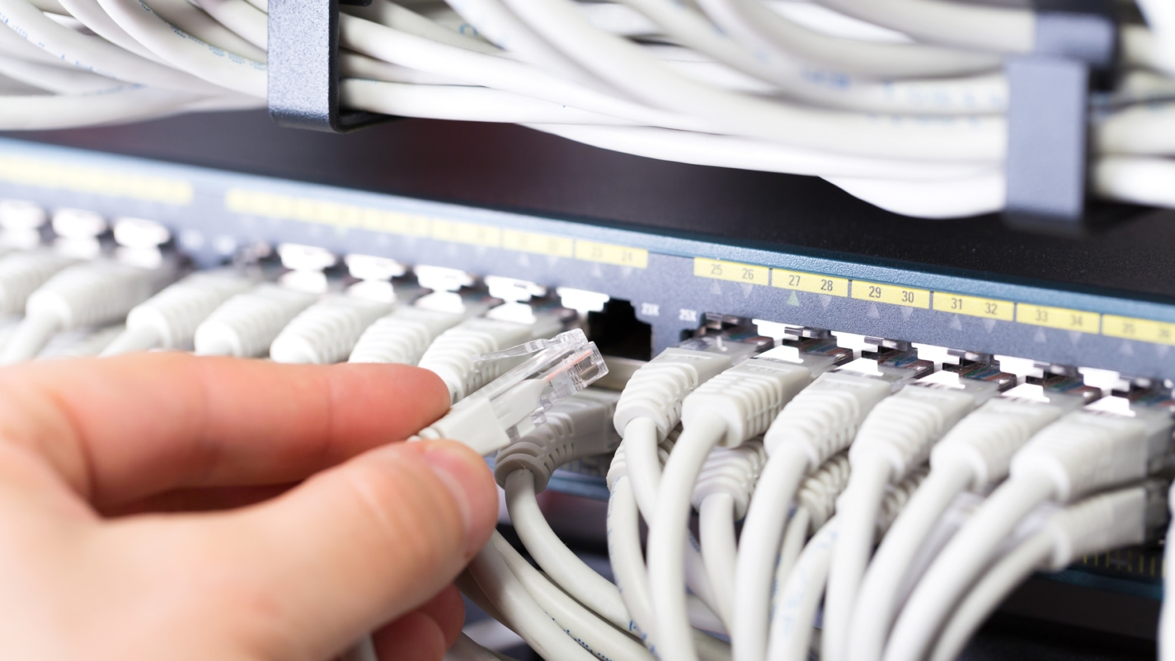 IT consultant connects a network cable into switch in datacenter by kjekol