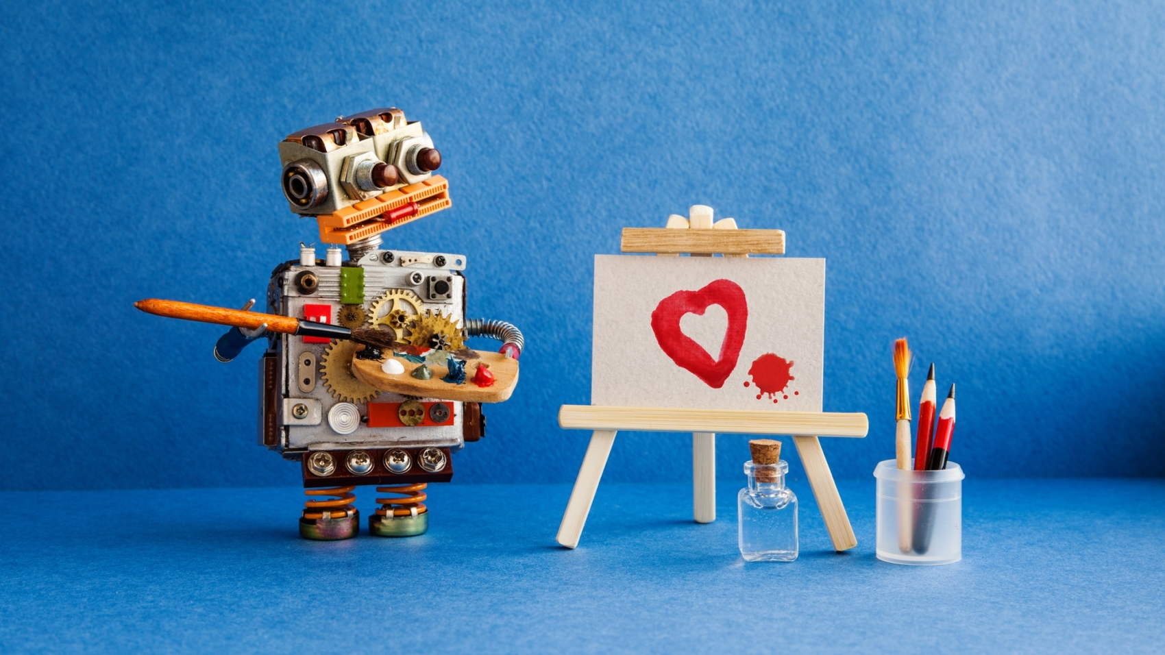 Robot artist with brush in hand looks at the red heart and a blot painted in watercolor on white paper and a wooden easel. Advertising poster studio school of visual arts and drawing. Artist's tools palette, pencils case. Blue background.