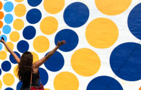 happy woman in front of a wall with colorful circles colors by @mylove4art