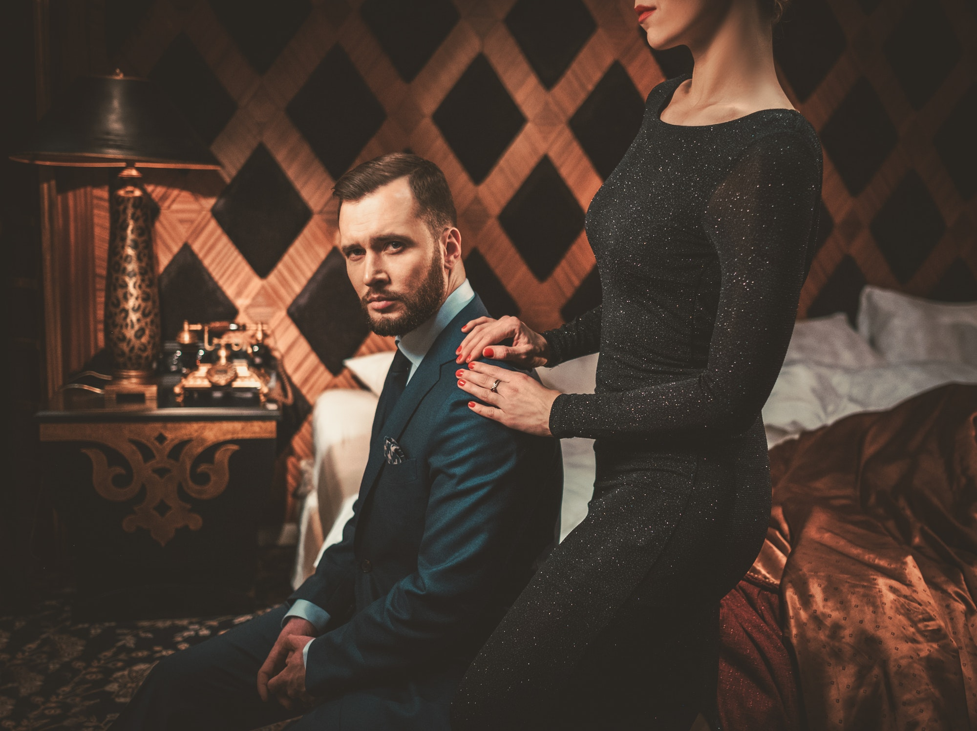 Well-dressed couple in luxury bedroom interior.