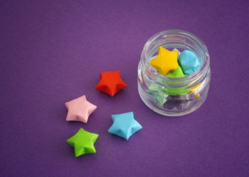 Colorful origami lucky stars spilling out of a jar