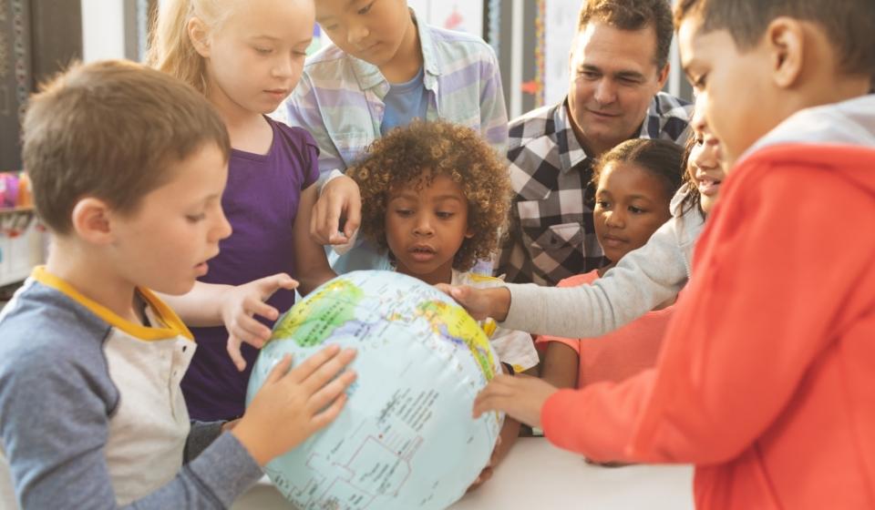 Schoolteacher discusing over earth globe in classroom at school
