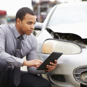 Loss Adjuster Using Digital Tablet In Car Wreck Inspection @monkeybusiness